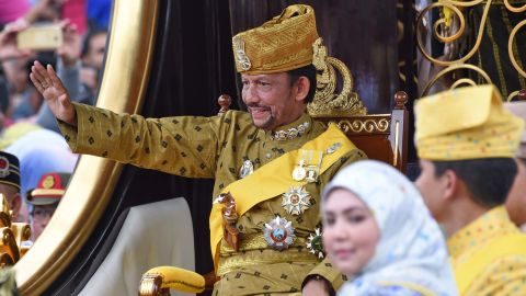 Brunei's Sultan Hassanal Bolkiah waves from the royal chariot during his golden jubilee procession