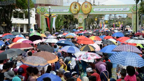 People wait under umbrellas for the royal chariot at jubilee celebrations.