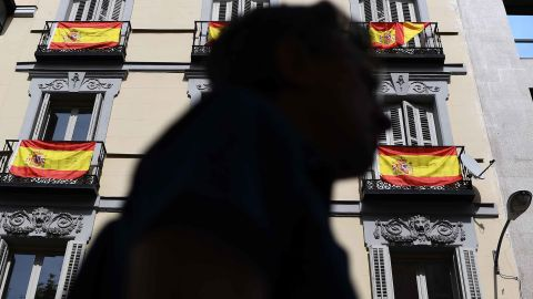 A man walks past a building with Spanish flags hanging from the balconies in Madrid, on September 30, 2017. Thousands of people, many waving red and yellow Spanish flags, rallied in Madrid in favour of Spanish unity today, a day before an banned independence referendum in Catalonia. / AFP PHOTO / GABRIEL BOUYS        (Photo credit should read GABRIEL BOUYS/AFP/Getty Images)