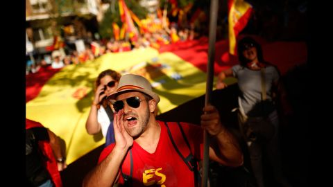 Demonstrators hold Spanish flags and shout slogans as they gather near a headquarters of federal police in Barcelona, Spain, Sunday Oct. 8, 2017. Demonstrators gathered early in Barcelona on Sunday ahead of a march to show support for the Spanish union and call on Catalonia not to declare independence. (AP Photo/Francisco Seco)