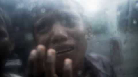 TOPSHOT - A young Rohingya Muslim refugee begs for food through the glass of a car at Balukhali refugee camp in Bangladesh's Ukhia district on October 7, 2017.A top UN official said Saturday Bangladesh's plan to build the world's biggest refugee camp for 800,000-plus Rohingya Muslims was dangerous because overcrowding could heighten the risks of deadly diseases spreading quickly. The arrival of more than half a million Rohingya refugees who have fled an army crackdown in Myanmar's troubled Rakhine state since August 25 has put an immense strain on already packed camps in Bangladesh. / AFP PHOTO / FRED DUFOUR        (Photo credit should read FRED DUFOUR/AFP/Getty Images)