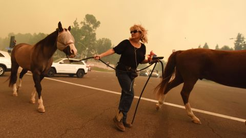 A woman moves horses in Orange as strong Santa Ana winds blow smoke from the Canyon 2 fire toward them on October 9.