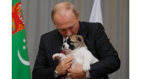 Russian President Vladimir Putin kisses a puppy he received from Turkmenistan President Gurbanguly Berdimuhamedov.