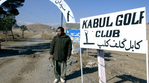 """Kabul Golf Club describes itself as the """"best and only"""" course in Afghanistan and promises """"golf with an attitude."""" An armed security guard stands beside the entrance."""