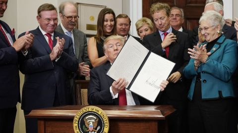 US President Donald Trump shows an executive order which he just signed on health insurance on October 12, 2017 in the Roosevelt Room of the White House in Washington, DC. / AFP PHOTO / MANDEL NGAN        (Photo credit should read MANDEL NGAN/AFP/Getty Images)