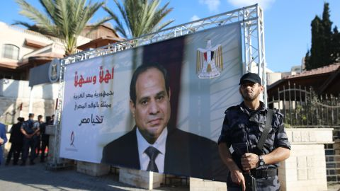 A Palestinian security guard loyal to Hamas stands next to a billboard bearing the portrait of Egyptian President Abdel Fattah al-Sisi near the Palestinian government headquarters in Gaza City on October 3, 2017. / AFP PHOTO / MOHAMMED ABED        (Photo credit should read MOHAMMED ABED/AFP/Getty Images)