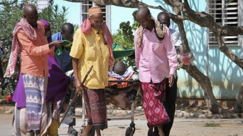 Somalis help an injured person. Hospitals struggled to cope with the high number of casualties, security and medical sources said.