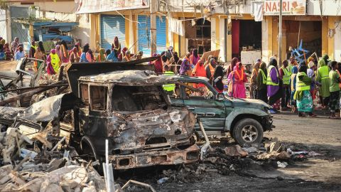People gather near burnt vehicles in the aftermath of the blast in Mogadishu.