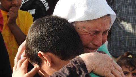 Marwan, 11, weeps into the crook of his grandmother's neck after reuniting with his family for the first time in 3 years.