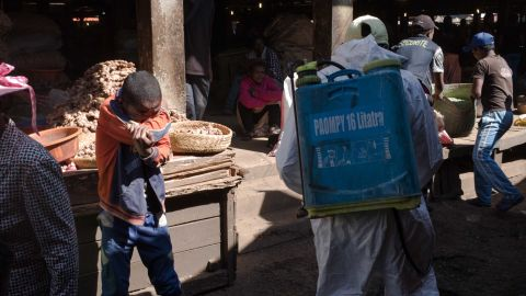 A boy covers his mouth as a council worker sprays disinfectant during the clean-up of the market in the Anosibe district, one of the most unsalubrious districts of Antananarivo.