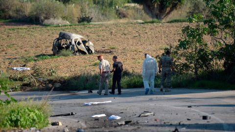 Investigators scour the scene after a bomb on Caruana Galizia's car  detonated on October 16, 2017.