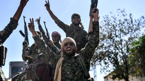 Members of the Syrian Democratic Forces (SDF), backed by US special forces, celebrate at the frontline in the Islamic State (IS) group jihadists crumbling stronghold of  Raqa on October 16, 2017 US-backed fighters battled  hundreds of Islamic State group jihadists holed up in the last pockets of Syria's Raqa, as the former extremist stronghold stood on the verge of capture. / AFP PHOTO / BULENT KILIC        (Photo credit should read BULENT KILIC/AFP/Getty Images)