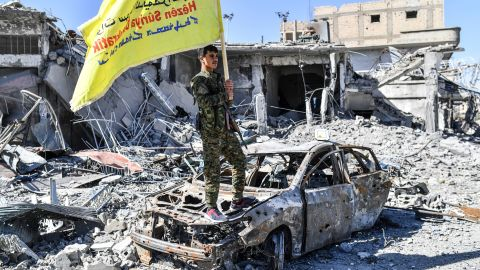 """A member of the Syrian Democratic Forces (SDF), backed by US special forces, holds their flag at the iconic Al-Naim square in Raqa on October 17, 2017. US-backed forces said they had taken full control of Raqa from the Islamic State group, defeating the last jihadist holdouts in the de facto Syrian capital of their now-shattered """"caliphate"""". / AFP PHOTO / BULENT KILIC        (Photo credit should read BULENT KILIC/AFP/Getty Images)"""