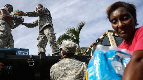 SAN ISIDRO, PUERTO RICO - OCTOBER 17:  U.S. Army soldiers pass out water, provided by FEMA, to residents in a neighborhood without grid electricity or running water on October 17, 2017 in San Isidro, Puerto Rico. The food and water delivery mission included U.S. Army, U.S. Coast Guard and Puerto Rico Hacienda forces. Residents said this was the first official governmental delivery of food and water to the community, nearly four weeks after the hurricane hit. Puerto Rico is suffering shortages of food and water in areas and only 17.7 percent of grid electricity has been restored. Puerto Rico experienced widespread damage including most of the electrical, gas and water grid as well as agriculture after Hurricane Maria, a category 4 hurricane, swept through.  (Photo by Mario Tama/Getty Images)
