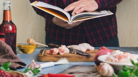 Man prepares chicken wings with cranberry sauce in a home kitchen