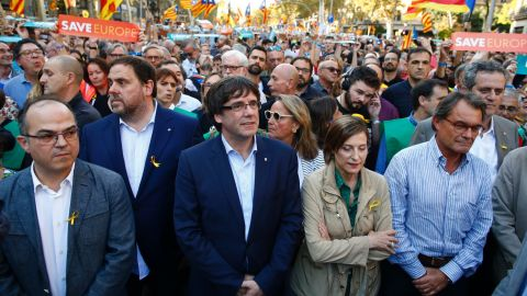 Catalan President Carles Puigdemont, center, takes part in an independence march in Barcelona on October 21.