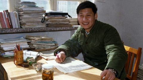 Xi poses for a photo as he sits in his office in 1983.