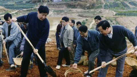 Xi, front left, helps reinforce a levee of the Minjiang River in 1995.