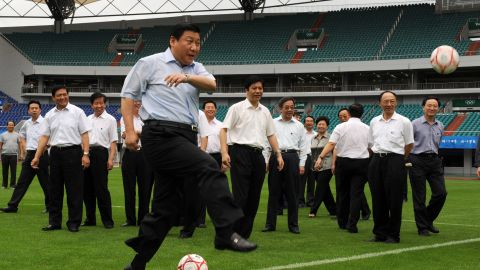 Xi kicks a soccer ball in 2008 as he inspects a field in Qinhuangdao, China. The stadium was hosting games during the 2008 Summer Olympics.