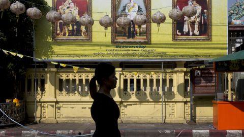 A woman walks past portraits of the late Thai King Bhumibol Adulyadej, left, and King Maha Vajiralongkorn, on Thursday in Bangkok.