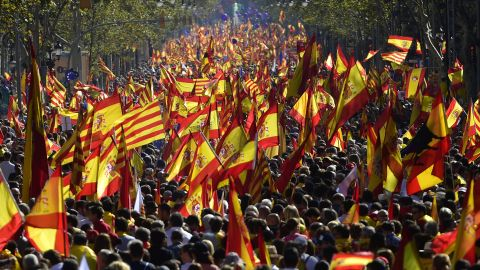 Protesters wave Spanish and Catalan flags during a pro-unity rally in Barcelona on October 29, 2017.