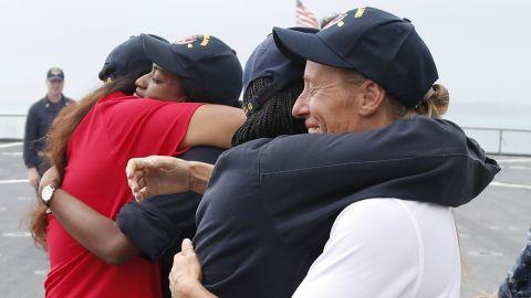 Jennifer Appel, right, and Tasha Fuiava hug crew members of the USS Ashland on the ship's deck.