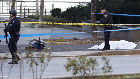 A New York Police Department officer stands next to a body covered under a white sheet near a mangled bike along a bike path Tuesday Oct. 31, 2017, in New York. (AP Photo/Bebeto Matthews)
