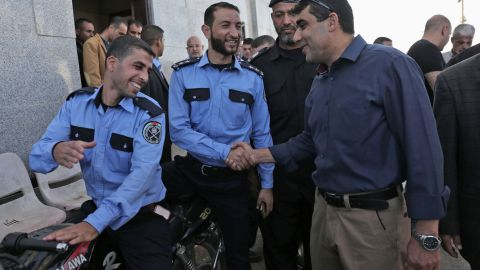 A member of the Palestinian Authority (R) shakes hands with security officers at the Rafah border crossing on Wednesday.