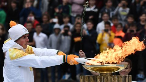 After completing a week-long tour of Greece, the flame was officially passed to the PyeongChang organizing committee at a handover ceremony. Greek Alpine skier Ioannis Proios is shown holding the torch at the ceremony in Athens' Panathenaic Stadium on October 31, 2017.