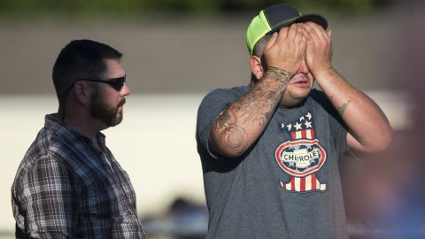 A man wipes his eyes after the shooting.