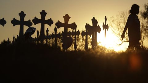 Miranda Hernandez pays her respects as she visits a makeshift memorial with crosses placed near the scene of a shooting at the First Baptist Church of Sutherland Springs, Monday, Nov. 6, 2017, in Sutherland Springs, Texas. A man opened fire inside the church in the small South Texas community on Sunday, killing over 20 and wounding many. (AP Photo/Eric Gay)