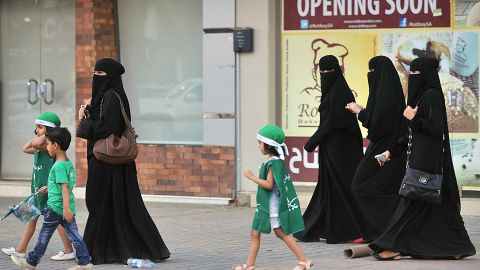 Saudi women and their children walk along a street as they make their way to a celebration rally marking the 83rd Saudi Arabian National Day.