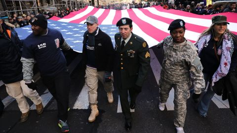 Soldiers, veterans and civilians carry an American Flag as they march in the Veterans Day Parade in New York City.