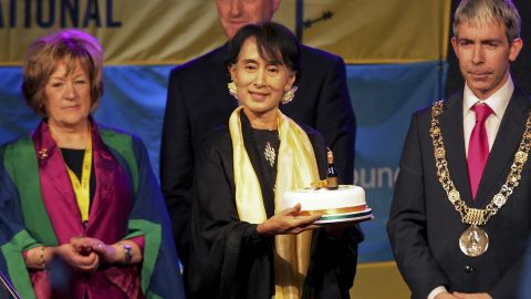 """Suu Kyi holds a birthday cake at the ceremony where she received the """"Freedom of the City of Dublin"""" award in Dublin in June 2012."""