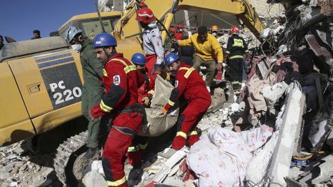 Members of the emergency services carry away the body of an earthquake victim in Sarpol-e-Zahab on November 14.