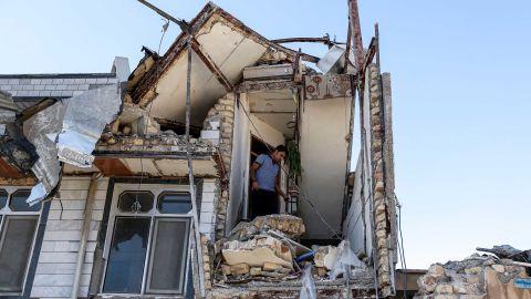 A man searches through a damaged building in Sarpol-e Zahab.