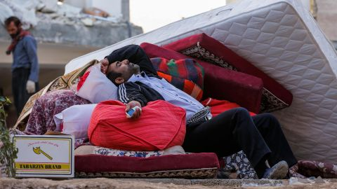 A man rests atop salvaged belongings in Sarpol-e Zahab.