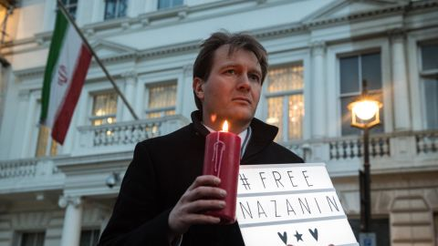 """Richard Ratcliffe holds a """"#Free Nazanin"""" sign and candle during a vigil for his wife outside the Iranian Embassy in London in January 2017."""