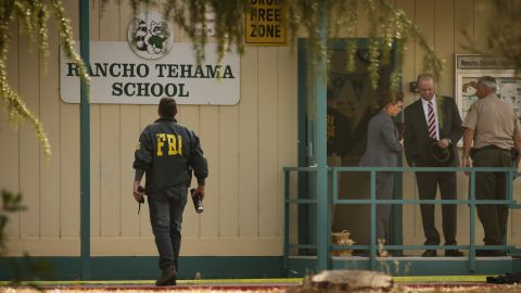 FBI agents are seen behind yellow crime scene tape outside Rancho Tehama Elementary School after a shooting in the morning on November 14, 2017, in Rancho Tehama, California Four people were killed and nearly a dozen were wounded, including several children, when a gunman went on a rampage at multiple locations, including a school in rural northern California. / AFP PHOTO / Elijah Nouvelage        (Photo credit should read ELIJAH NOUVELAGE/AFP/Getty Images)