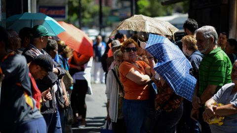 People queue outside a supermarket in Caracas to buy basic foodstuffs and household products on November 10, 2017. In crisis-stricken Venezuela, the cost of the basic basket of goods soared to nearly 2.7 million bolivars in September, the equivalent of six minimum monthly wages.