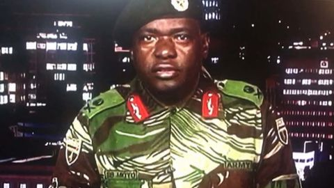 """In a screen grab of a TV broadcast on the Zimbabwe Broadcasting Corp., Maj. Gen. Sibusiso Moyo reads a statement saying the military was conducting an operation to target """"criminals"""" close to the President who were causing """"social and economic suffering."""" He denied a coup was underway."""