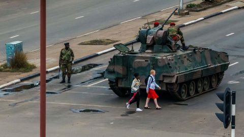 Two pedestrians pass behind an armored personnel carrier stationed at an intersection in Harare on November 15.