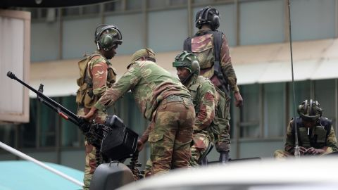 Members of the military check a gun as they stand atop an armored vehicle parked in Harare's central district on November 16.