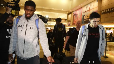UCLA basketball players Cody Riley, left, LiAngelo Ball, right, and Jalen Hill, background center, are surrounded by the media as they leave the Los Angeles International Airport on Tuesday, Nov. 14, 2017, in Los Angeles. The three UCLA basketball players detained in China on suspicion of shoplifting returned home, where they may be disciplined by the school as a result of the international scandal.