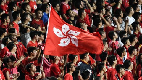 Local football fans hold up the Hong Kong flag during a match against Malaysia in Hong Kong on October 10, 2017.