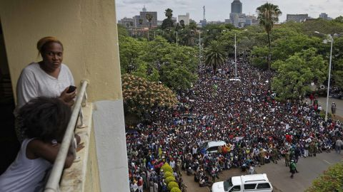 A woman and her daughter look out from their balcony as a crowd of protesters gather on the road leading to the State House in Harare on Saturday, November 18.