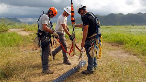 Whitefish Energy Holdings workers repair power line towers after the passing of Hurricane Maria in Manati, Puerto Rico on October 31, 2017. Whitefish Energy had won a $300-million contract to help turn the lights back on in Puerto Rico, where some 80 percent of customers still lack power more than a month after Hurricane Maria ripped through the island. But Puerto Rico is scrapping the deal with the tiny American firm that fell under intense scrutiny the head of its power authority said on October 29, 2017. / AFP PHOTO / Ricardo ARDUENGO        (Photo credit should read RICARDO ARDUENGO/AFP/Getty Images)