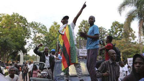 Zimbabweans raise their fists at the news of Robert Mugabe's resignation.