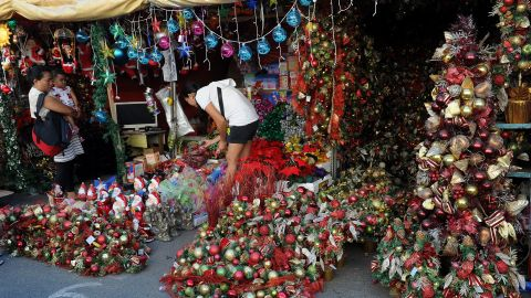 Customers buy Christmas decorations from a street stall at the farmer's market in suburban Manila.  The Philippines is Asia's bastion of Roman Catholicism and celebrates the world's longest Christmas season.