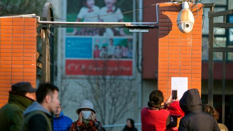 Parents take photos of a notice posted by the RYB kindergarten announcing measures taken in response to allegations of children abuse in Beijing, China.
